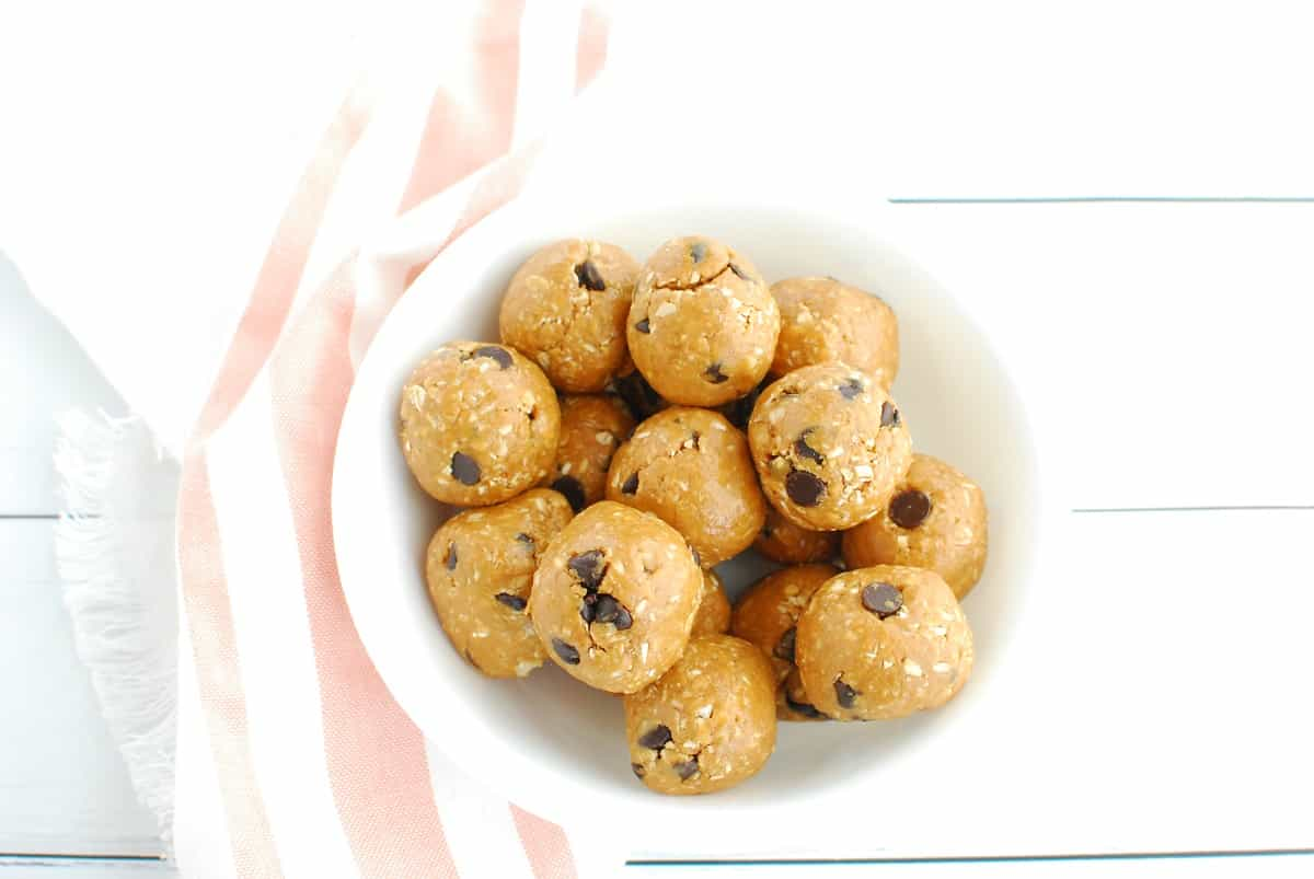 A white bowl full of healthy peanut butter cookie dough bites, next to a striped pink and white napkin.