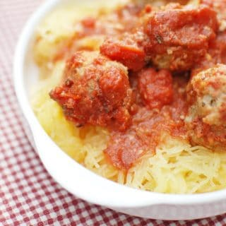 A plate with crockpot spaghetti squash and meatballs topped with tomato sauce