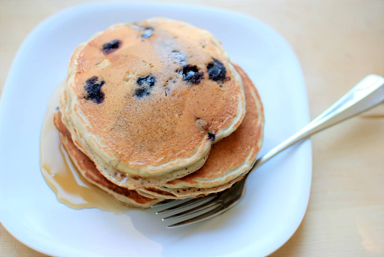 Blueberry greek yogurt pancakes on a plate with a fork
