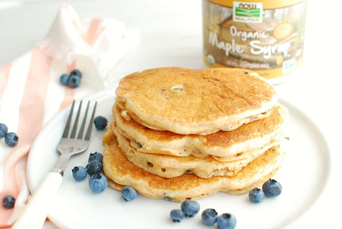 A stack of four blueberry Greek yogurt pancakes on a white plate, next to a fork and some scattered blueberries.