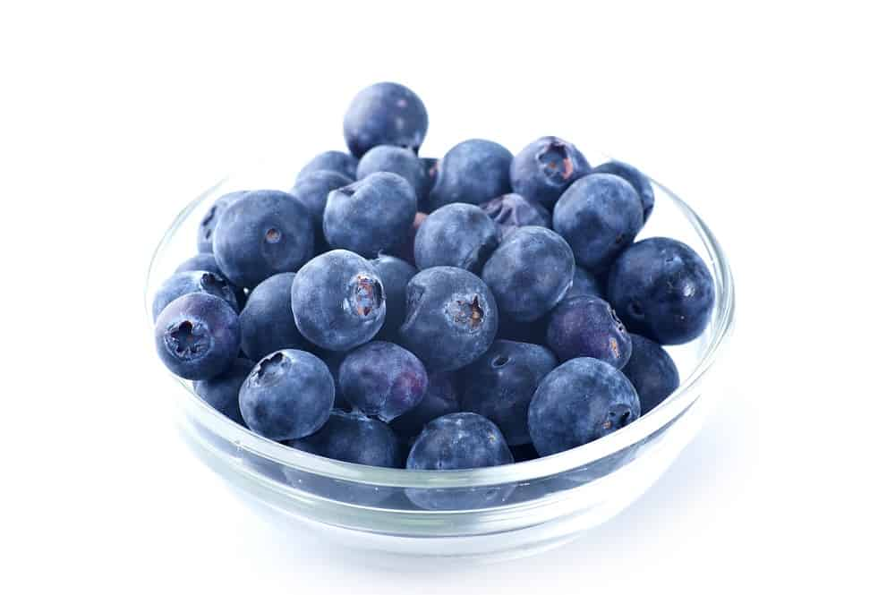A small glass bowl full of blueberries.