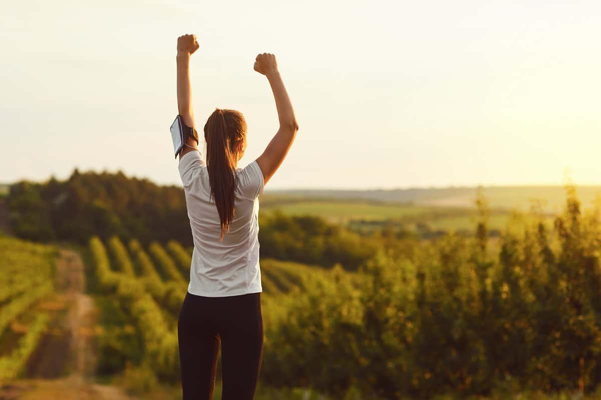 A runner raising her hands outside after a run, showing her love of running.