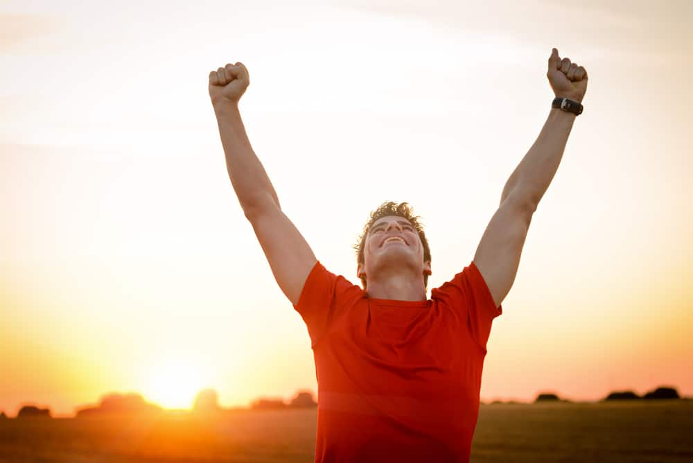 A male runner raising his hands in the air, happy after a run.