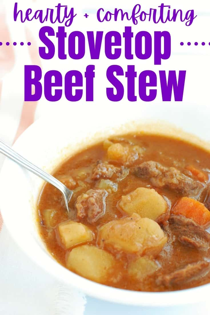 A white bowl with a spoon in it full of stovetop beef stew.