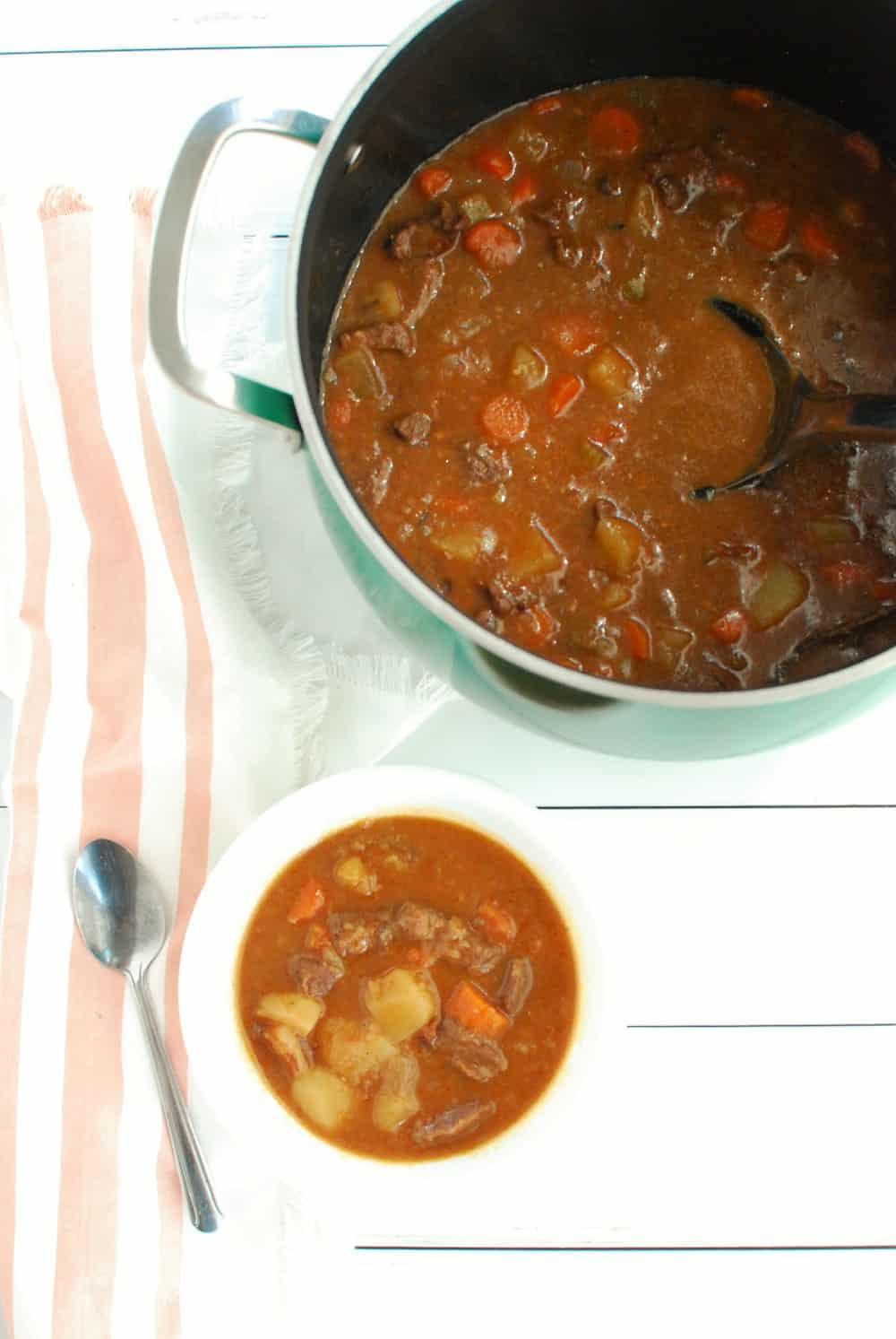 A bowl of beef stew next to a pot full of it.
