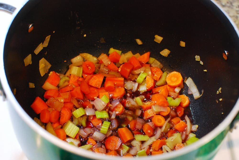 Carrots, celery, onions, and red wine in a pot.