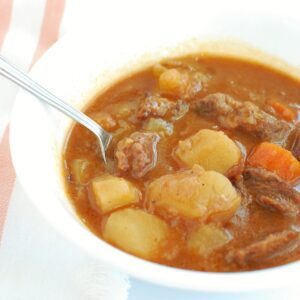A bowl of stovetop beef stew with a spoon in it.