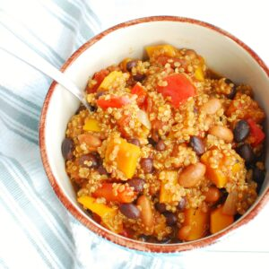 A bowl with butternut squash quinoa chili next to a napkin.