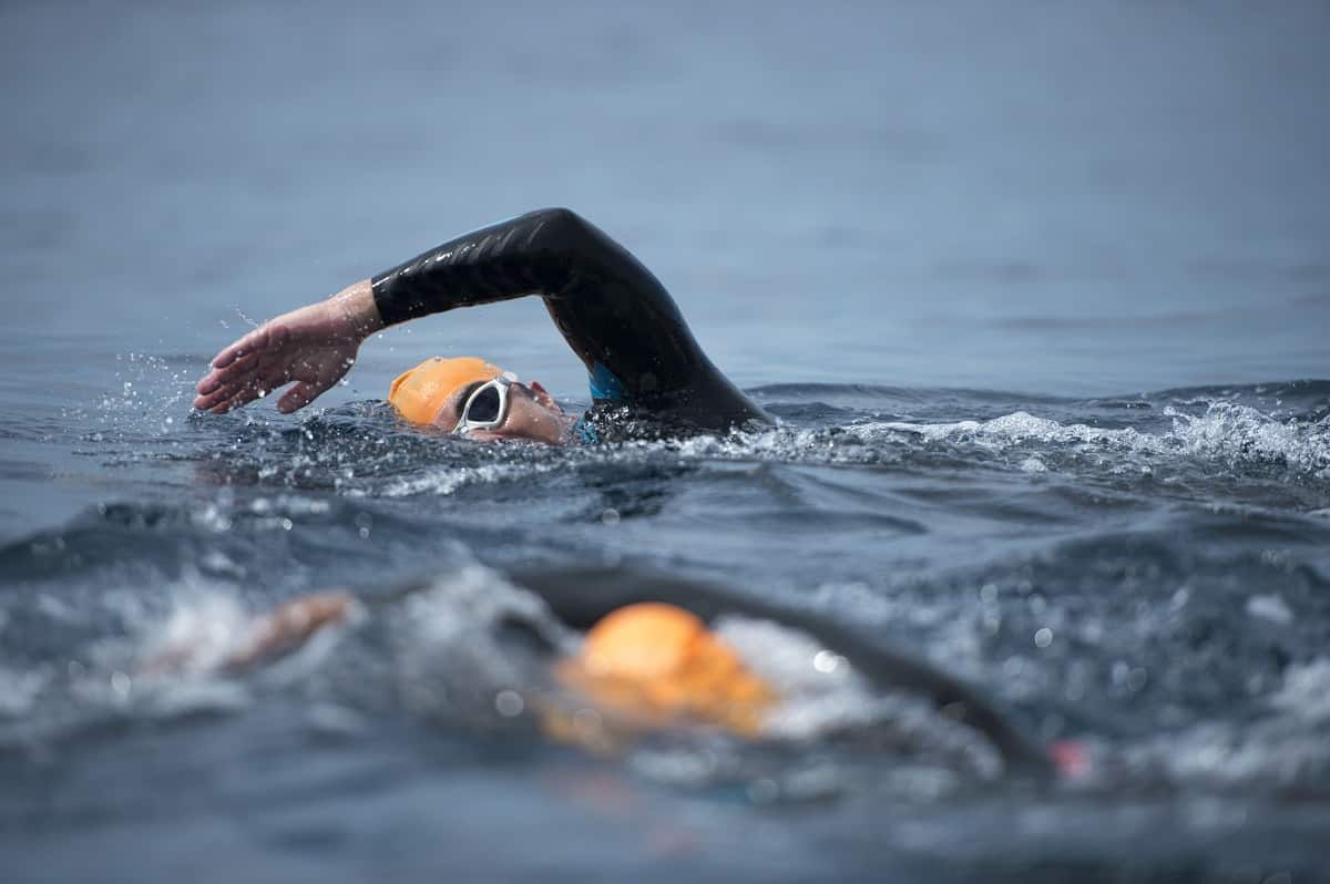 A man swimming in open water during his first triathlon.