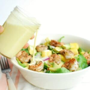 A woman holding a jar of creamy citrus salad dressing, pouring it onto a shrimp salad.