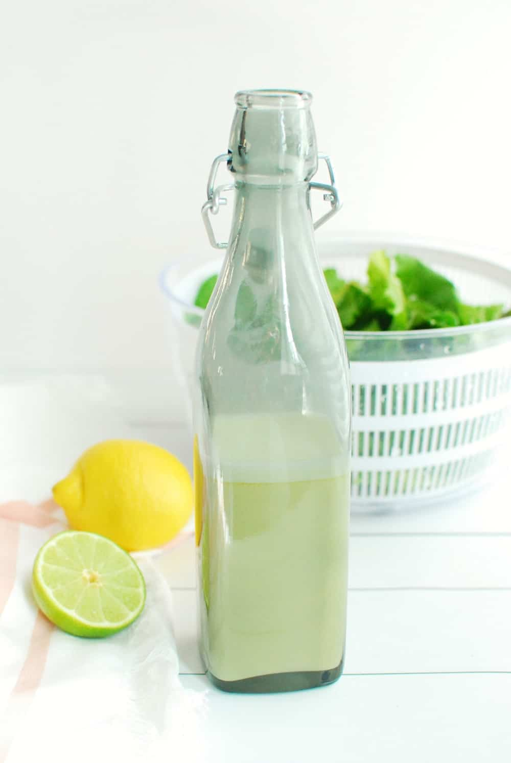 A bottle of salad dressing next to a sliced lime and a napkin.