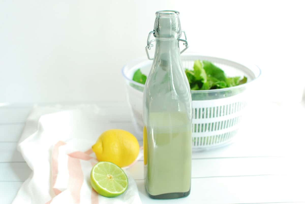 A salad dressing bottle filled with creamy citrus dressing, next to a lemon, lime, and leafy greens.