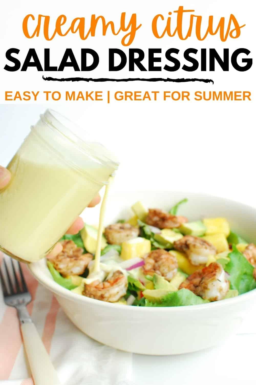 A woman pouring citrus salad dressing over a shrimp salad.