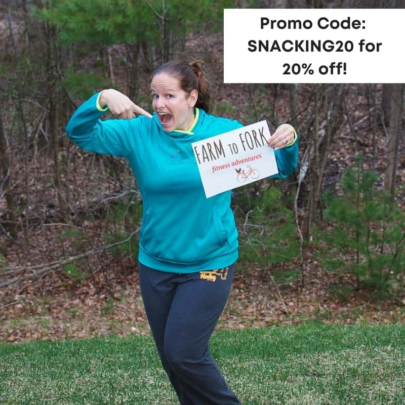 A woman holding a sign with a Farm to Fork Fondo promo code.