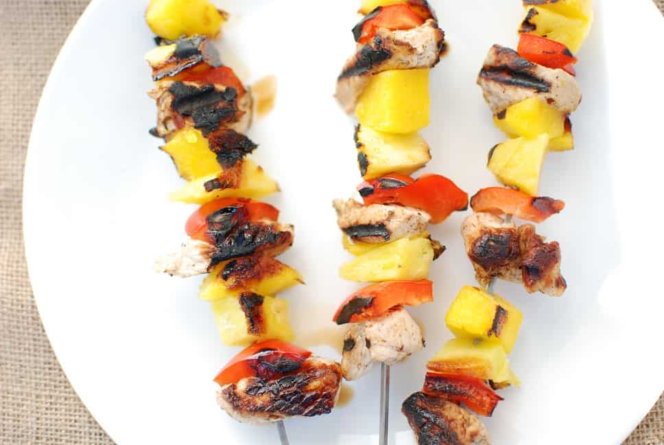 Three grilled turkey skewers with peppers and pineapple on a white plate