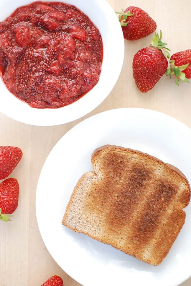 A piece of toast next to strawberry chia seed jam