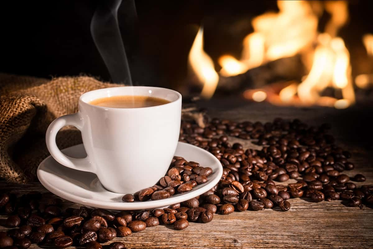 A cup of coffee next to some coffee beans with a fireplace in the background.