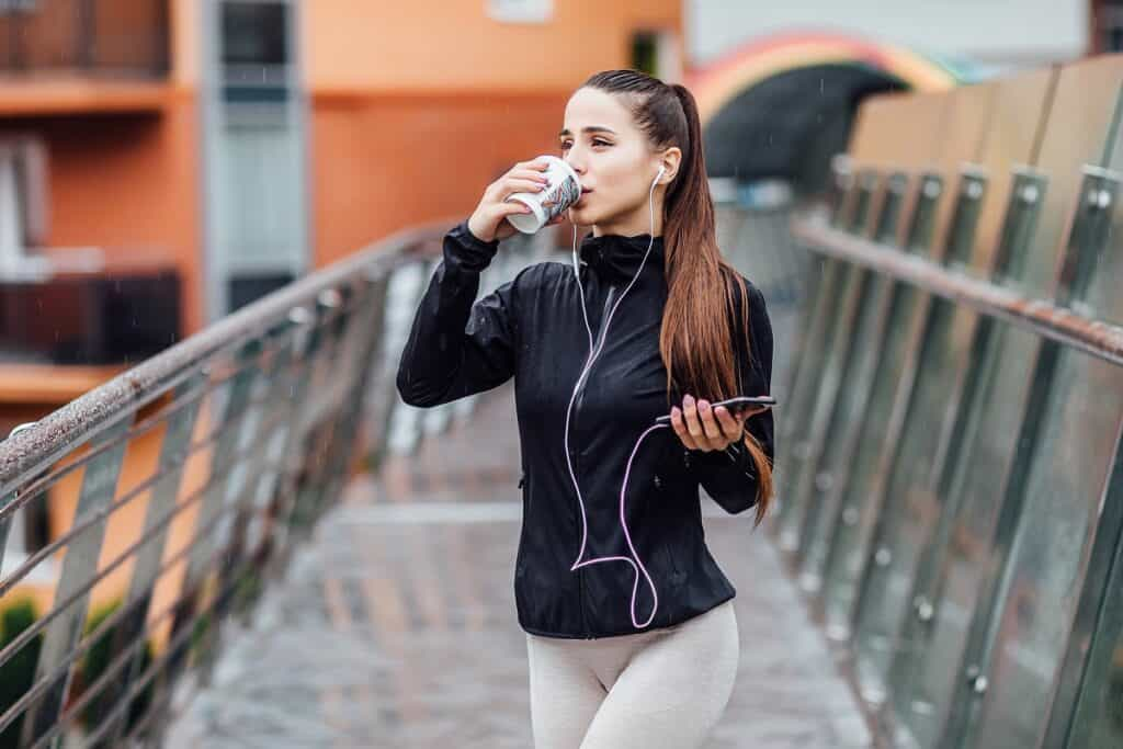 A woman drinking coffee before running, standing outside with headphones on and wearing athletic clothes.