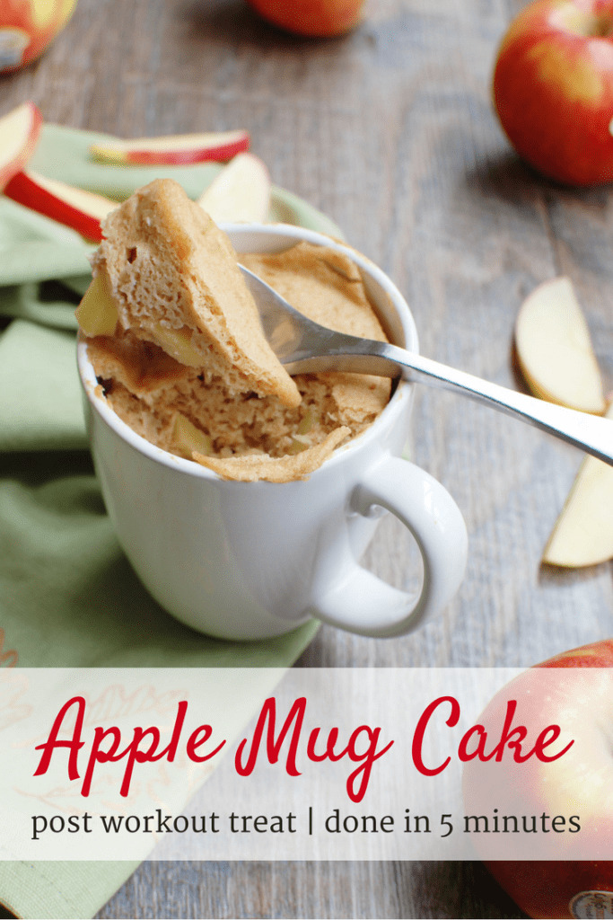 an apple mug cake in a white cup next to sliced apples