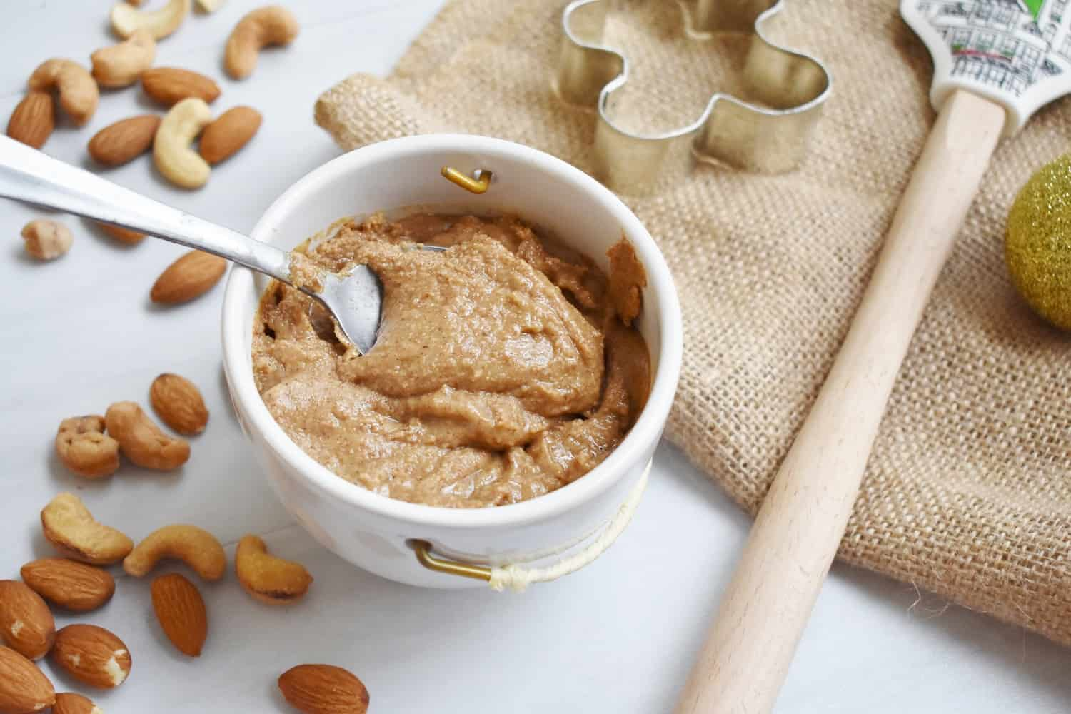 Homemade gingerbread nut butter in a cup with a spoon