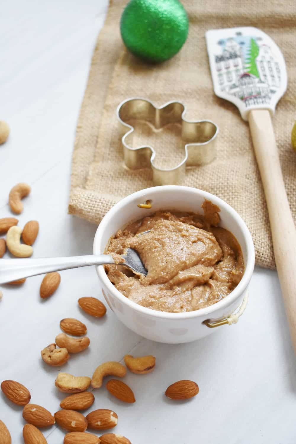 A cup full of homemade gingerbread almond cashew butter next to nuts