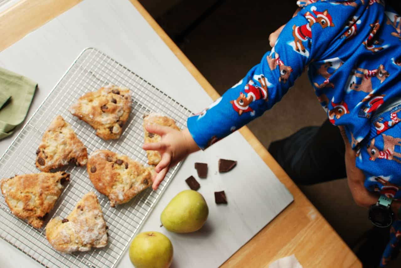 child reaching for a pear and chocolate scone