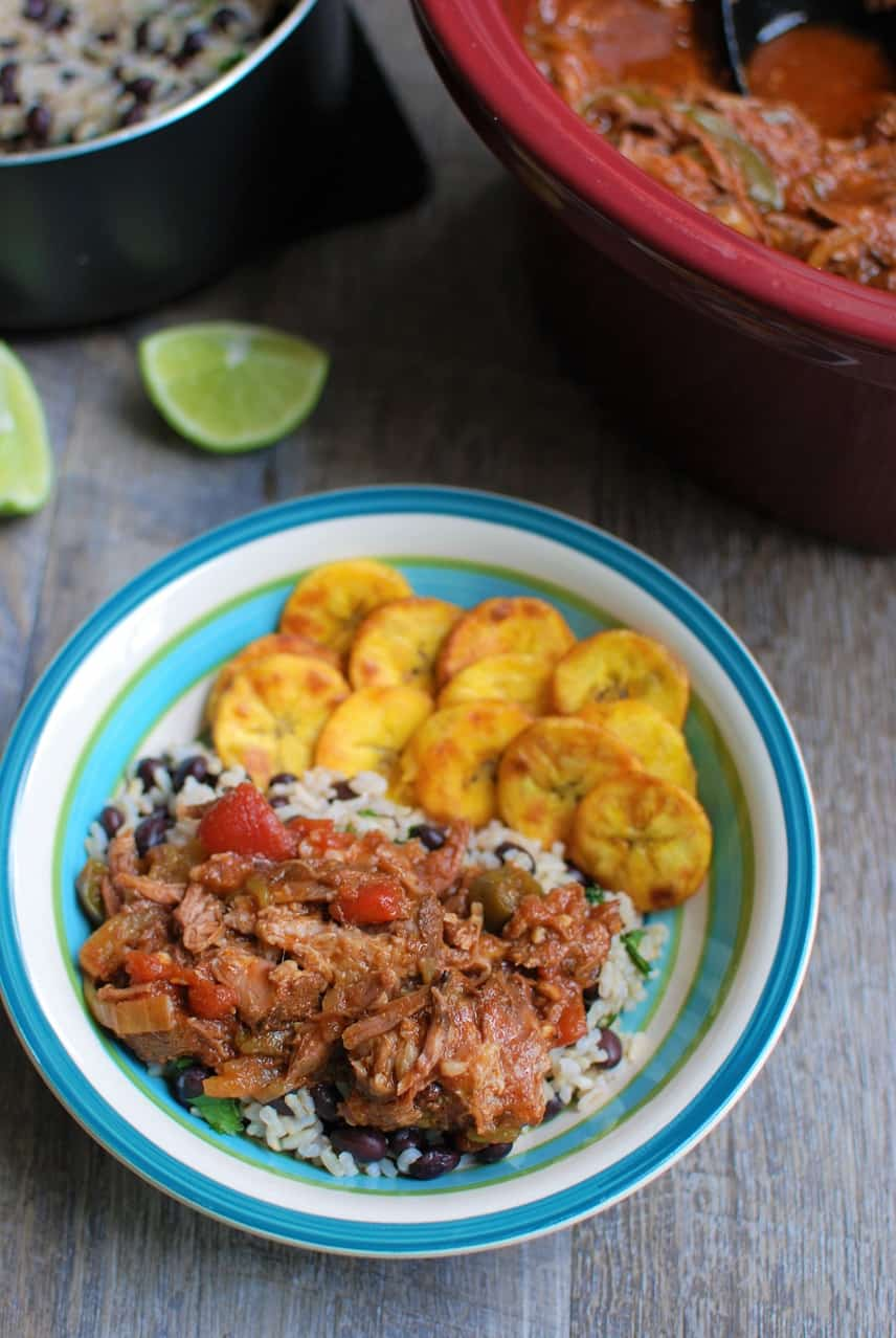 A bowl filled with rice, beans, ropa vieja, and fried plantains