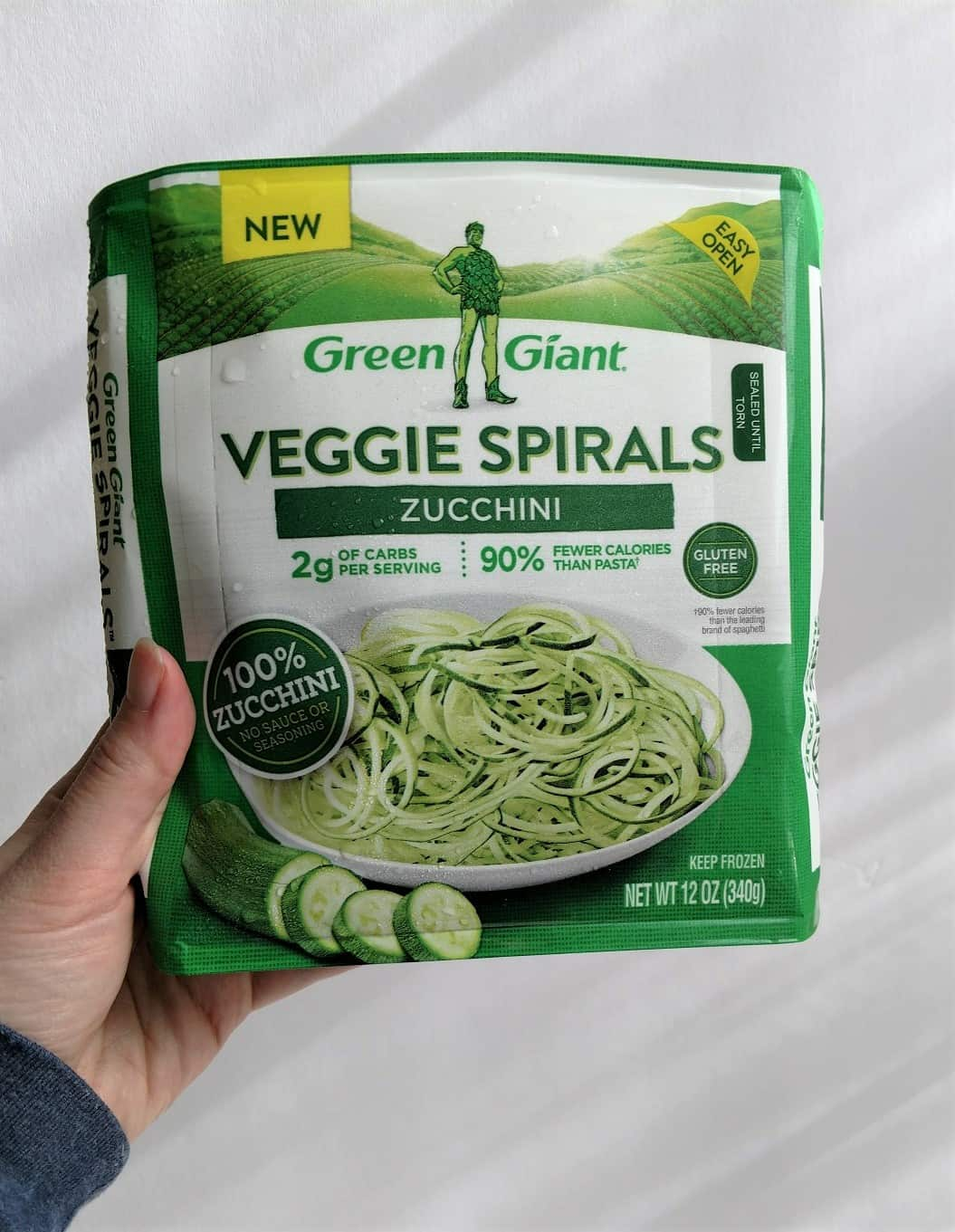 Hand holding a package of Green Giant Veggie Spirals zucchini noodles