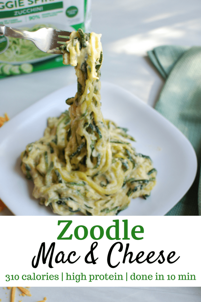 Fork lifting up zoodle macaroni and cheese from white plate