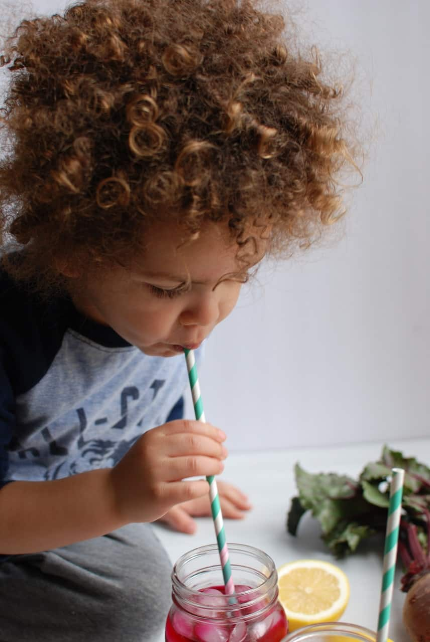 Child drinking beet lemonade from a straw
