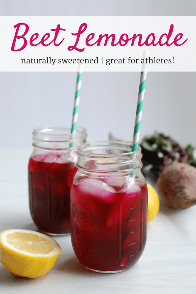 Two mason jars filled with beet lemonade next to a lemon and beet