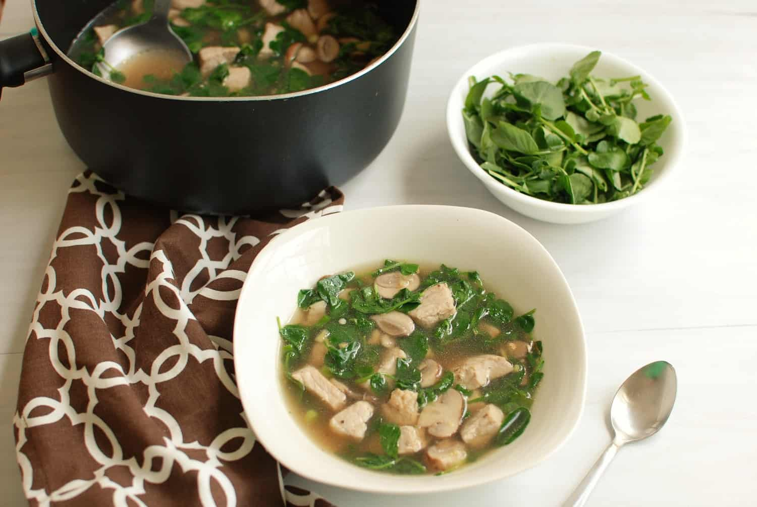 A bowl and pot of pork watercress soup, next to a bowl of watercress
