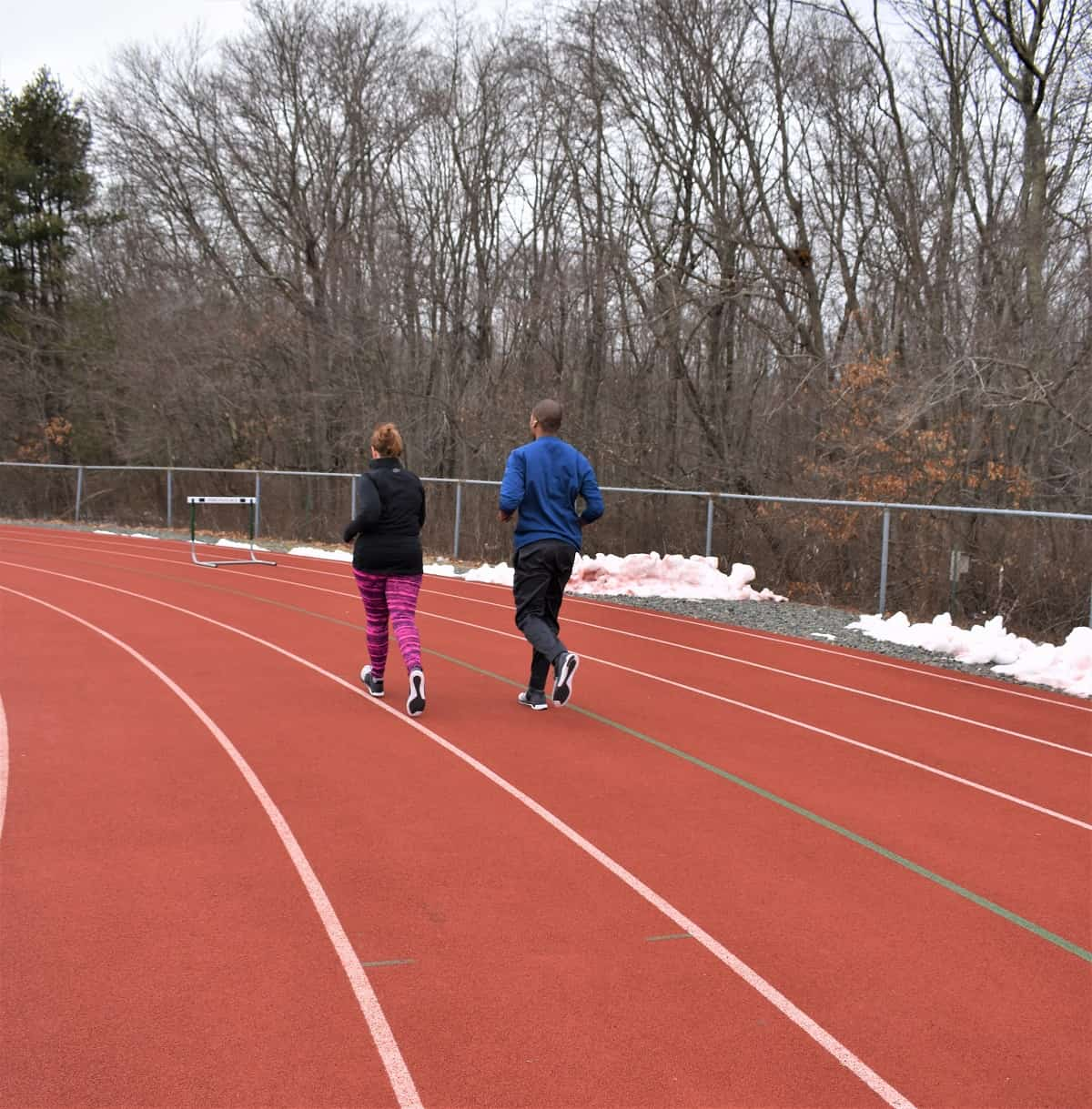 Couples running on a track in the winter