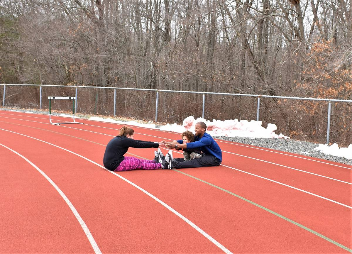 Couples stretching together on a track