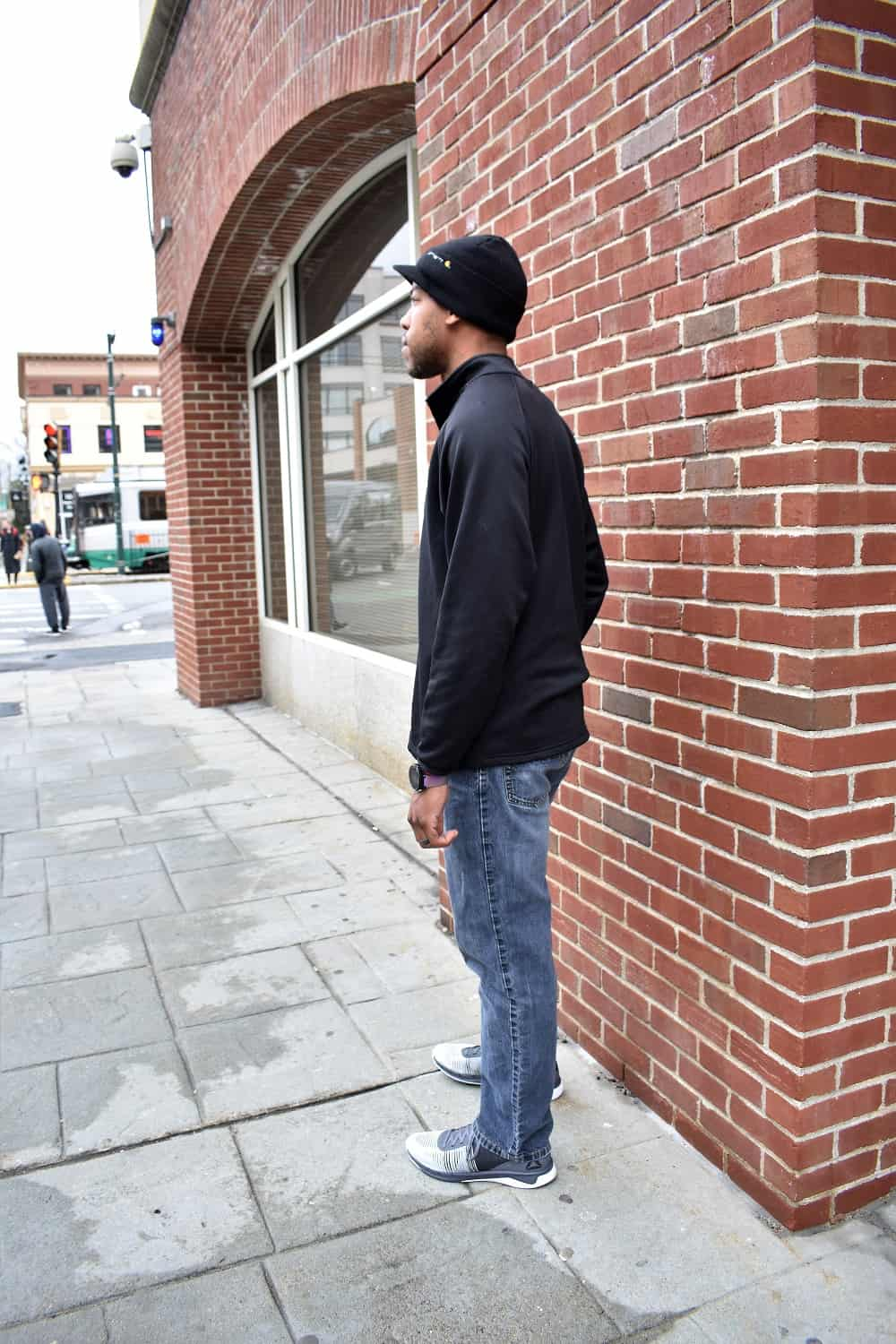 Man wearing black shirt, jeans, and sneakers in the city