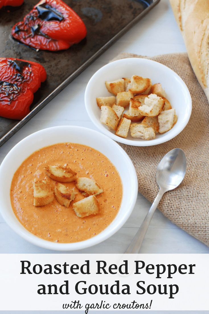 Roasted red pepper and gouda soup next to a bowl of croutons