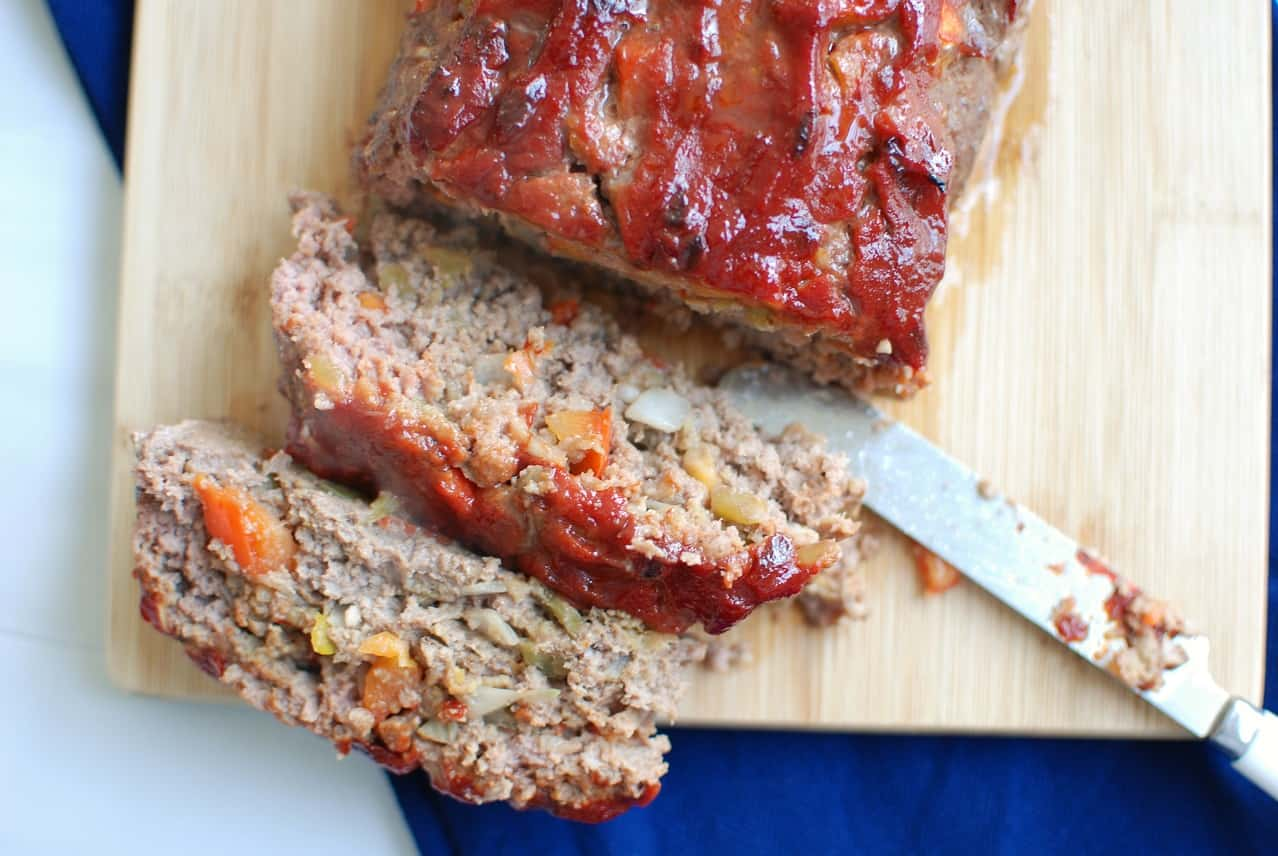 Green chile meatloaf on a cutting board with a few slices cut
