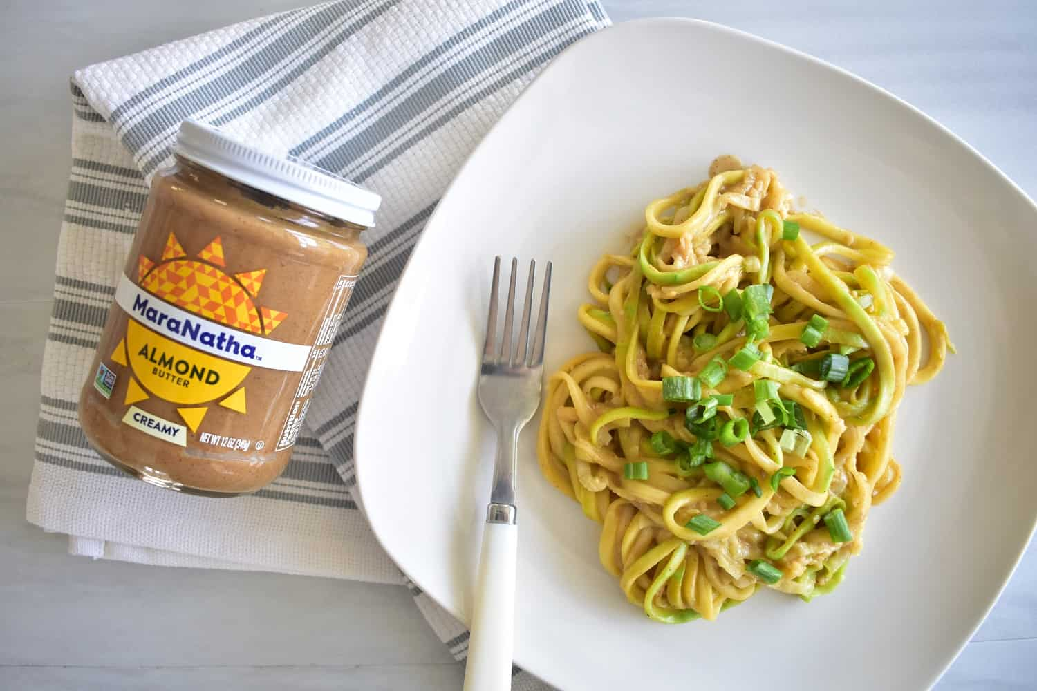 zucchini noodles with almond butter sauce on a plate next to a jar of almond butter