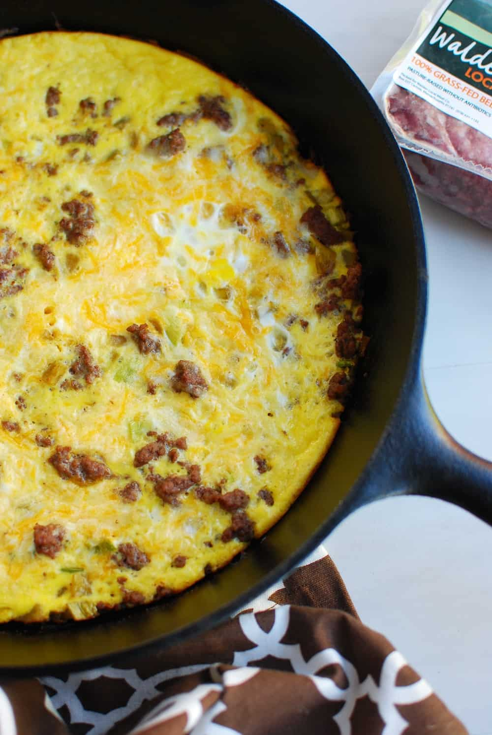 Keto frittata made with eggs, cheese, ground beef, scallions, and chiles