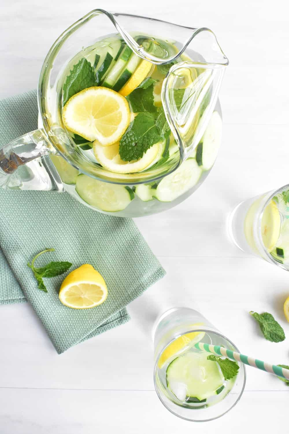 Pitcher and two glasses filled with lemon mint cucumber water