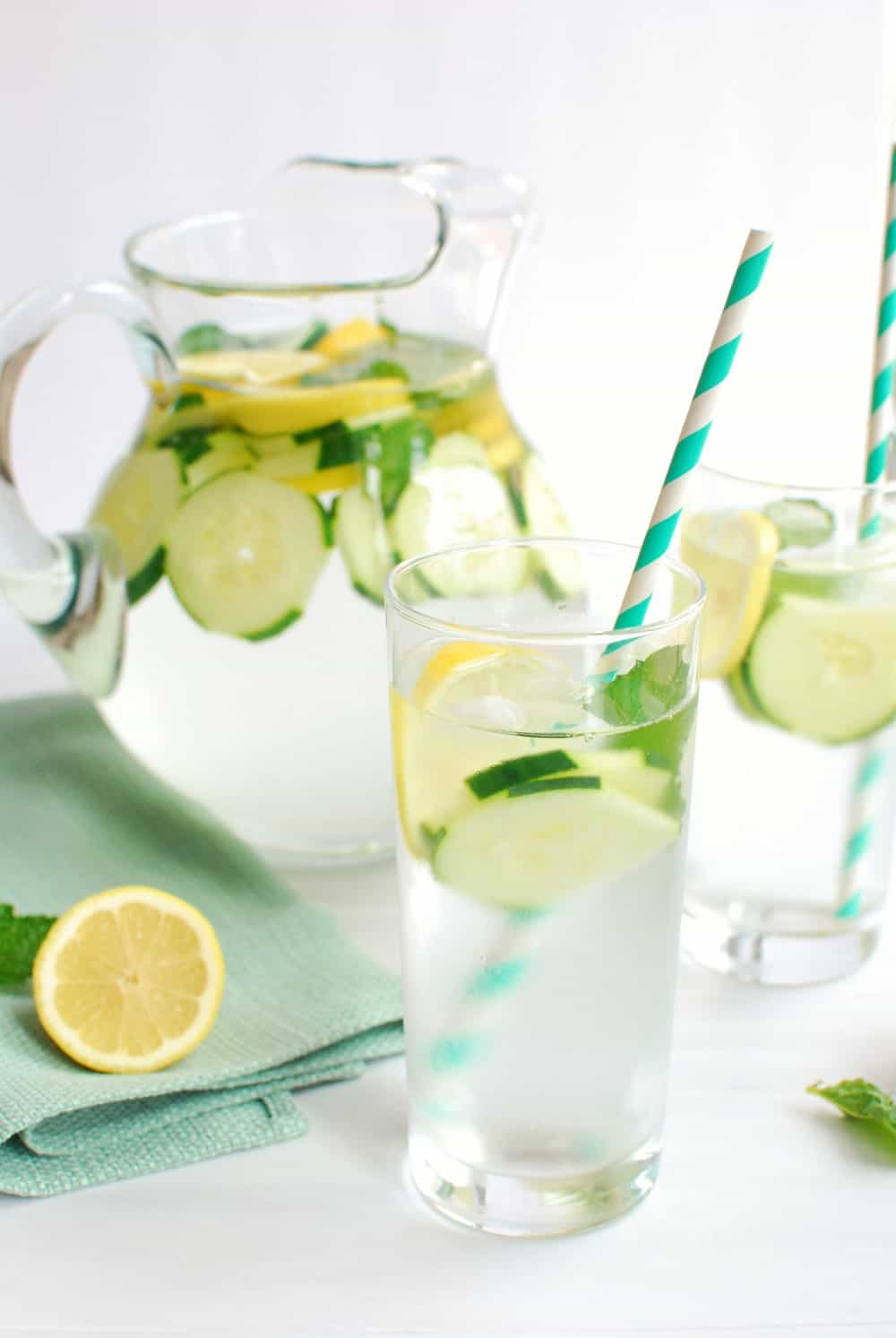 Glass of cucumber lemon mint water with a straw in it
