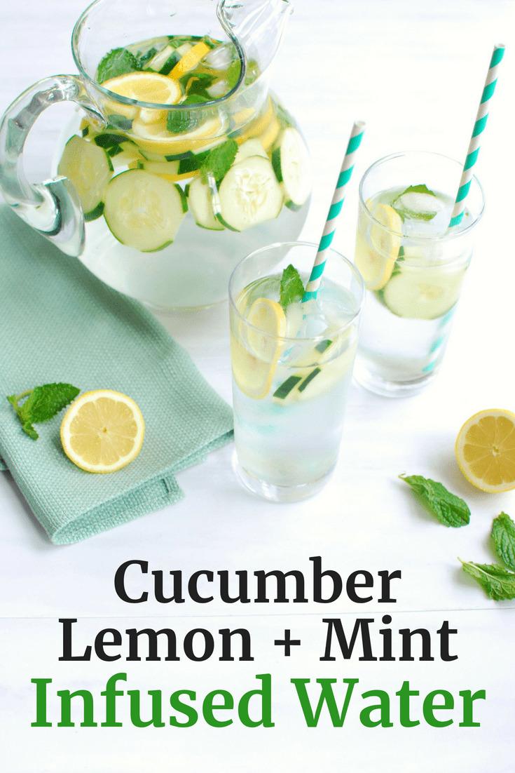 Pitcher full of cucumber lemon mint water, next to a sliced lemon
