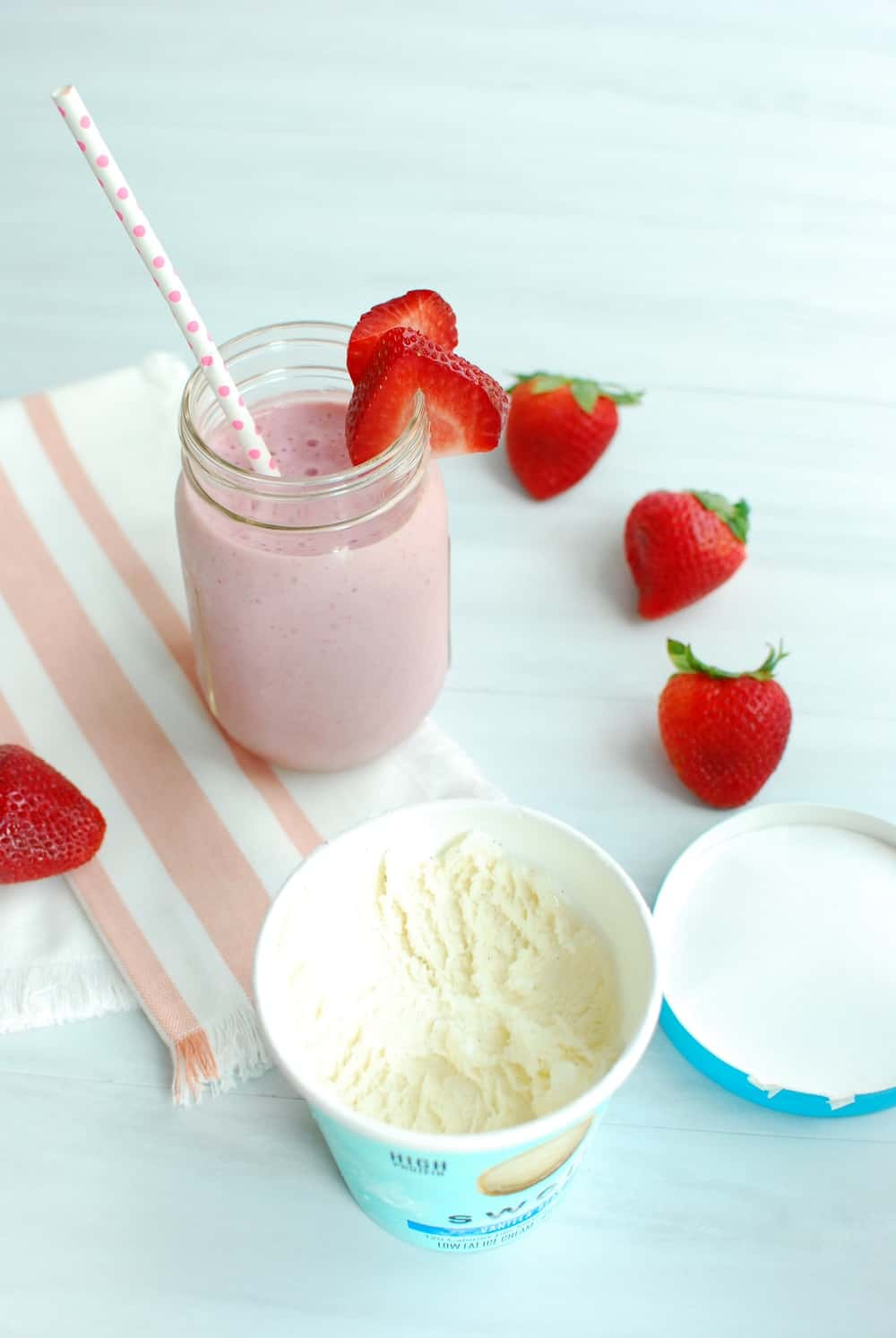 Open pint of ice cream next to a healthy strawberry milkshake