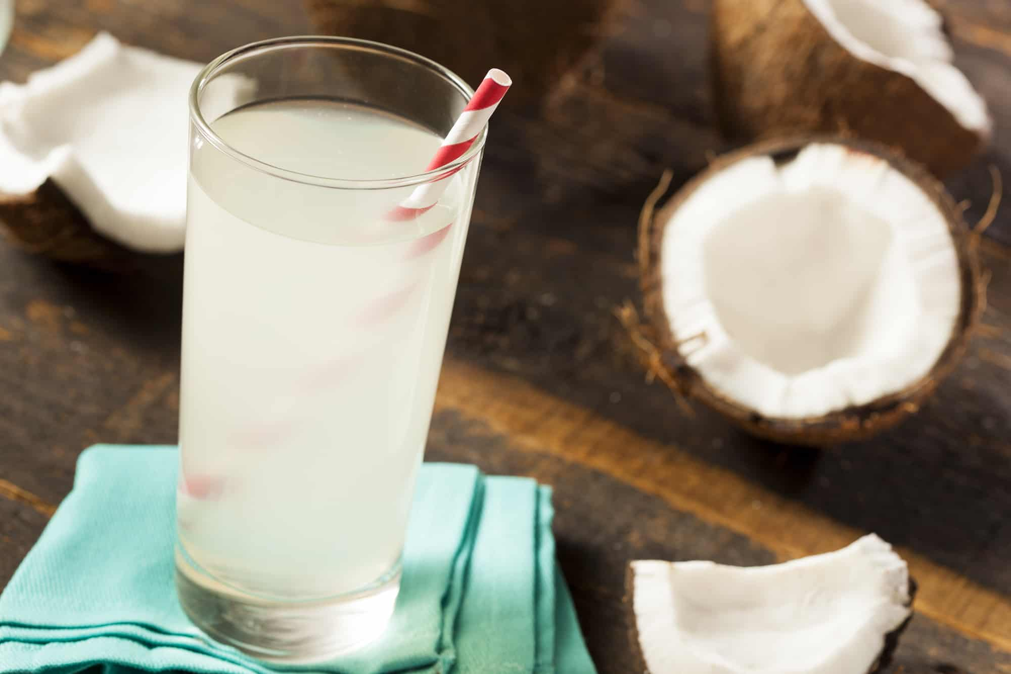 Fresh Organic Coconut Water for Runners Next to a Coconut