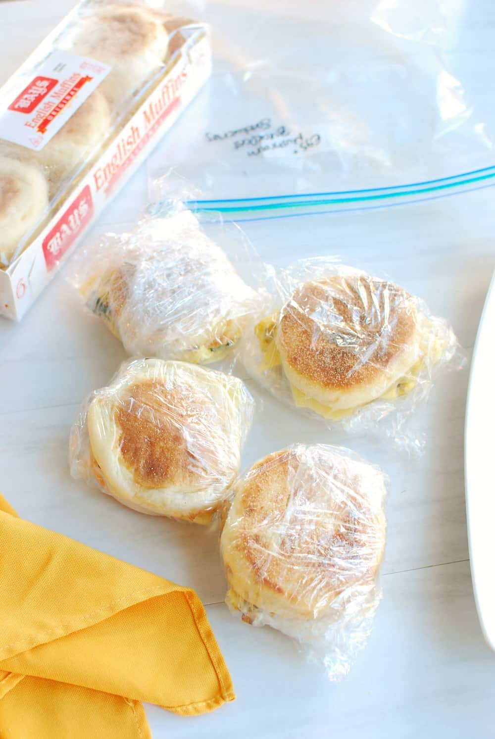 Four meal prep breakfast sandwiches being wrapped to put in the freezer