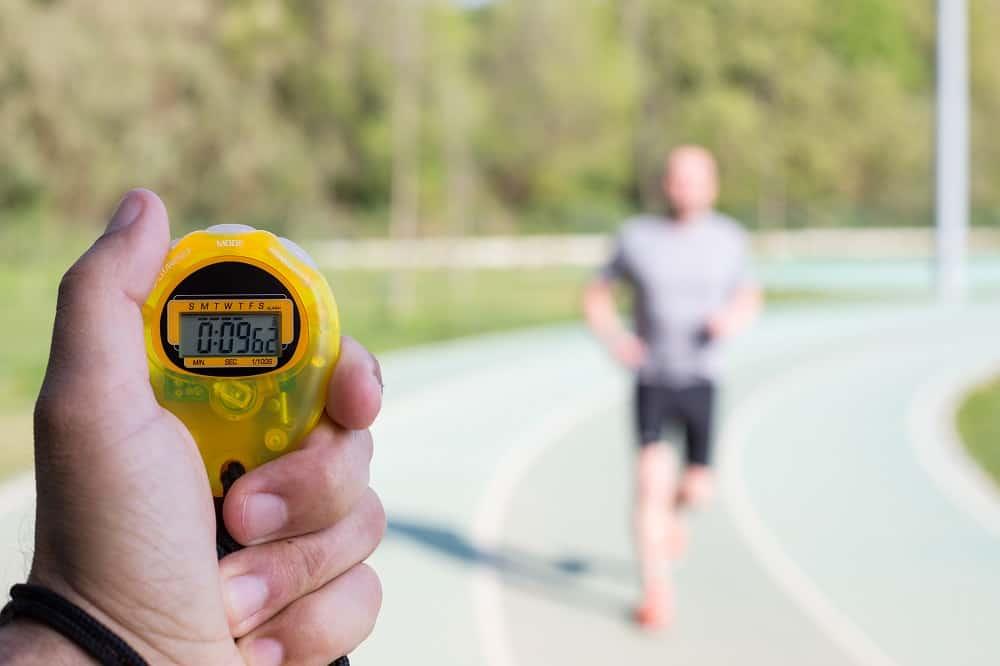 Triathlon coach clocking a workout