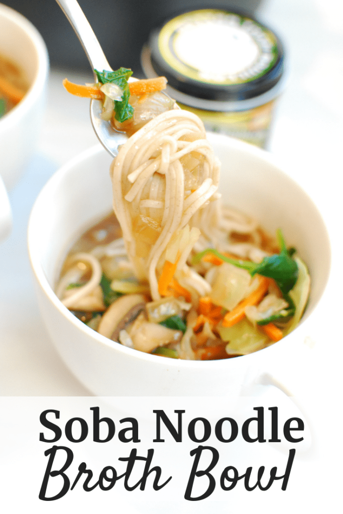 A spoonful of food from a soba noodle broth bowl