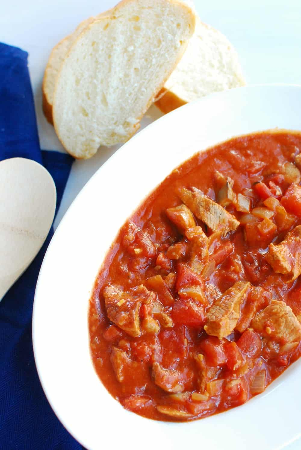 A large bowl full of veal marengo stew next to french bread