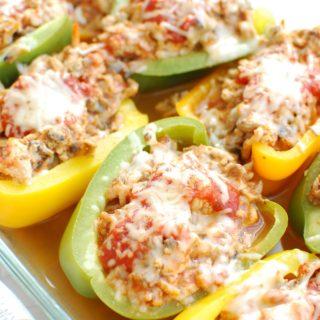 A casserole dish with cooked chicken stuffed peppers