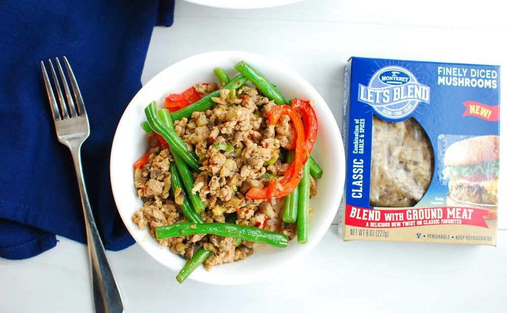 Szechuan pork in a bowl with green beans and mushrooms